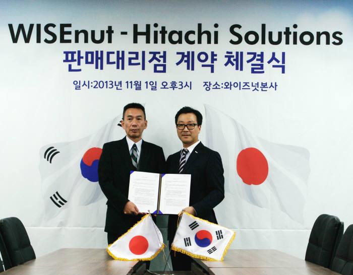 강용성 와이즈넛 대표(오른쪽)가 스즈키 카즈후미 히타치솔루션즈 본부장과 계약서를 들고 기념촬영을 하고 있다.