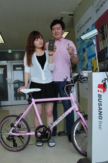 송준우 부상 대표(오른쪽)와 직원이 스마트폰 기반 무인자전거대여시스템을 시연하고 있다.