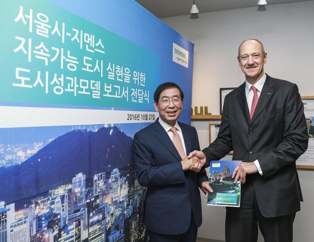27일 오후 서울 시청에서 열린 '도시성과모델 보고서' 전달식에서 롤랜드 부시 독일지멘스 부회장(오른쪽)과 박원순 서울시장(왼쪽)이 기념 촬영을 하고 있다.
