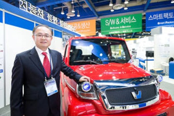 CEO Park Young-tae of CammSys Corp. is posing next to an electric pickup truck that was displayed at Korea Electronics Show.