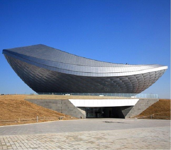 대구광역시 달성군에 위치한 디 아크(THE ARC, 건축가 하니 라시드 디자인). 잔잔한 물위에 돌을 튕겨 만드는 물수제비와 수면 위로 뛰어 오르는 물고기와  한국전통 도자기인 막사발을 표현