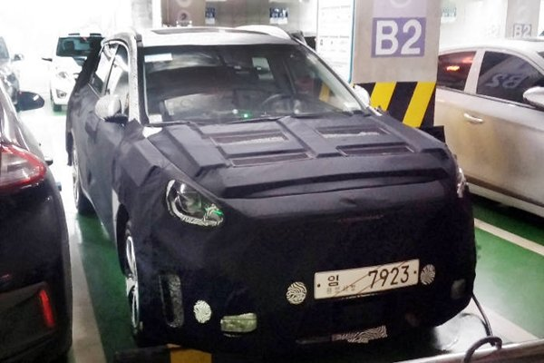 An electric vehicle, which is being test-driven, is being charged at an E-Mart that is located in Seongnam-si with a cover hiding it.  After gathering information, this vehicle is found to be Hyundai Motor Company's SUV electric vehicle that is expected to be released in 2018.