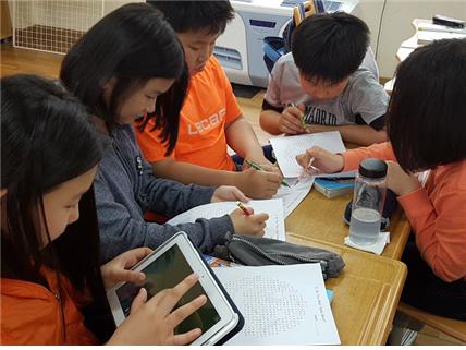 (한 학생은 마크를 쓰고, 다른 학생들은 학습지에서 단어를 찾고 있다.)