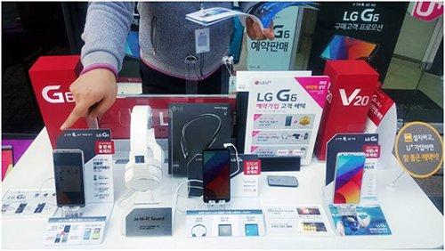 韩国首尔西大门区延世路附近的LG U+直销店店员正在介绍新产品功能(图片来源:韩国《电子新闻》)