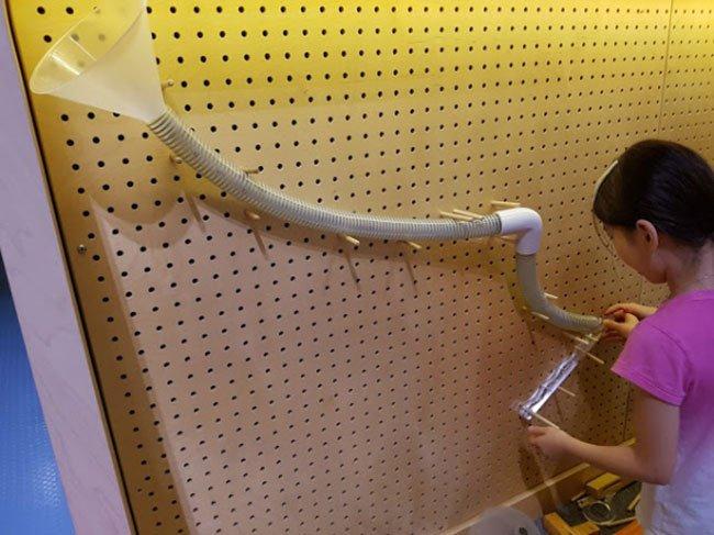 위에서 구슬이 내려오는 골드버그 장치를 통해 중력을 배우는 어린이