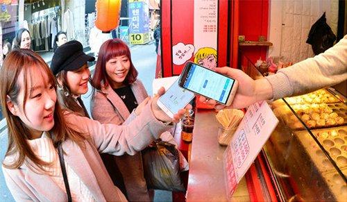 今年5月起,韩国首尔市传统市场将引进手机支付方式。3月23日,在韩国首尔麻浦区某露天商铺,顾客正在使用近距离无线通信支付方式进行Phone To Phone支付(图片来源:韩国《电子新闻》)