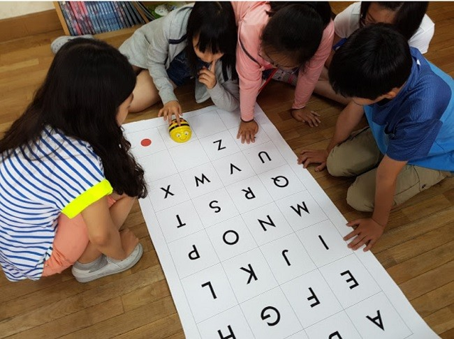한 학생이 알파벳이 있는 판에 비봇을 움직이기 위해 버튼을 누르고 있다.