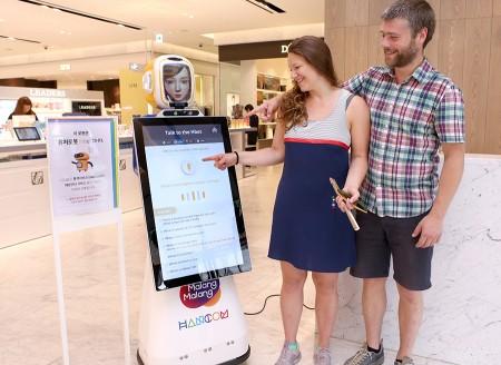 현대백화점은 유통업계 최초로 현대시티아울렛 동대문점에 인공지능 기반 통역 기술이 적용된 말하고 움직이는 로봇 쇼핑 도우미 '쇼핑봇'을 선보였다. 외국인 고객들이 쇼핑봇을 이용하고 있다. 사진=현대백화점 제공