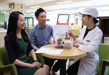 현대그린푸드 영양사가 직원식당에서 급식 이용 고객에게 그리팅 라이트 프로그램을 설명하고 있다. 사진=현대그린푸드 제공