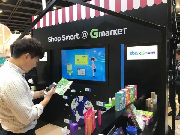 G마켓과 옥션, G9를 운영하는 전자상거래 기업 이베이코리아가 SBA(서울산업진흥원)와 협력해 국내 최초로 홍콩 메가쇼(MEGA SHOW)에서 '서울 중소기업 제품 O2O(Offline to Onlline) 체험존'을 운영해 주목을 받고 있다. 사진은 홍콩 메가쇼 하이서울 어워드 홍보관 내 설치한 'G마켓 글로벌샵 O2O체험존'에서 바이어들이 QR코드를 통해 스마트폰으로 제품을 구매하는 모습. O2O체험존에서 전시하는 제품들은 국내 최고 역직구 사이트 G마켓 글로벌샵에서 영·중문으로 실제 판매 중이다. 현장에서 QR코드를 스캔하면 관련 페이지로 연동돼 제품 구매가 가능하다.사진=이베이코리아 제공