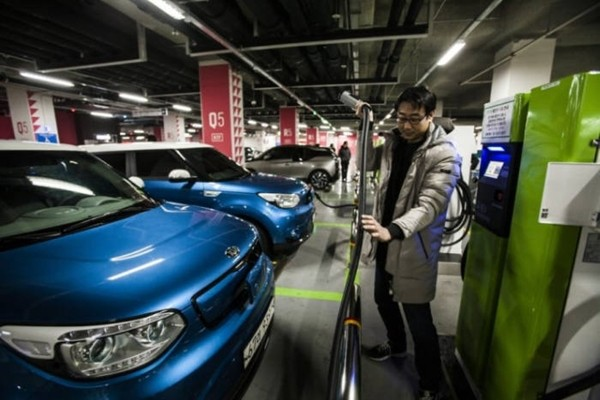 An owner of an electric vehicle is charging his electric vehicle using a charger that is set up in the underground parking lot of Lotte World Tower.