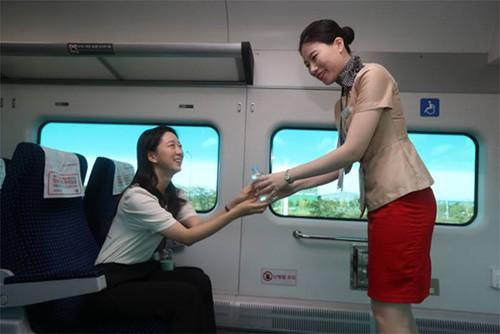 直达列车乘务员正在给乘客传递免费饮用水。