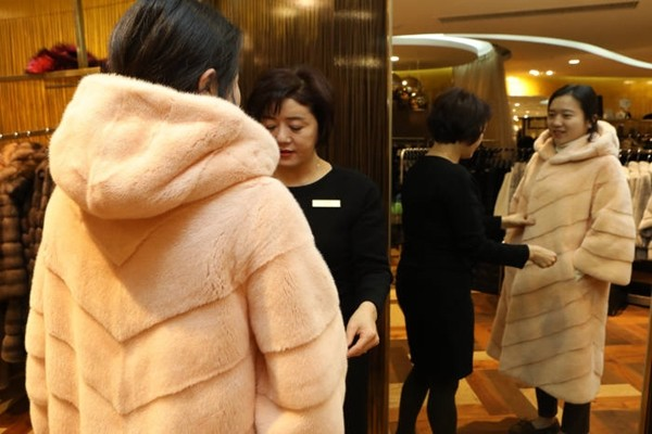 A customer is trying on a product at a fur coat store located at Lotte Department Store.