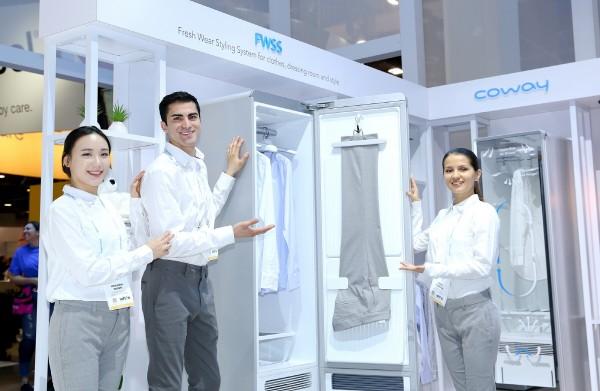 코웨이 모델들이 '2018 CES(Consumer Electronics Show)'에서 최초 선보이는 '코웨이 의류청정기 FWSS(Fresh Wear Styling System)'을 소개하고 있다. 사진=코웨이 제공