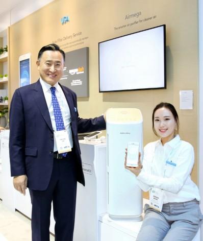 이해선 코웨이 대표이사(좌측)가 세계 최초로 공기청정기에 애플 스마트 플랫폼인 홈킷(Home Kit)을 연동한 공기청정기 '코웨이 Tower'를 소개하고 있다. 사진=코웨이 제공