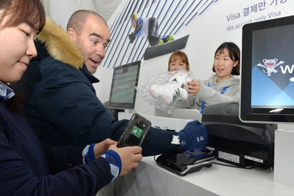 At a superstore in Gangneung on the 8th, which is the day before the opening day of Pyeongchang Winter Olympics, a foreigner is making a payment for a souvenir through wearable.  By showing interest to wearable payment, which takes by placing a glove, a sticker, or an Olympic badge near a card reader, he repeatedly made exclamation marks.  Staff Reporter Park, Jiho | jihopress@etnews.com