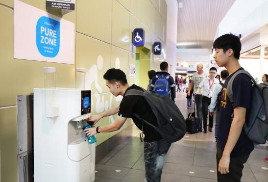 말레이시아 쿠알라룸푸르국제공항(Kuala Lumpur International Airport) 내 코웨이 정수기를 체험할 수 있는 'Pure Zone'에서 공항 이용객들이 코웨이 정수기로 정수한 깨끗한 물을 마시고 있다. 사진=코웨이 제공