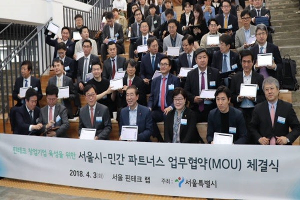 Mayor Park Won-soon of Seoul-si (fourth from the left), Director Kim Ki-sik of Financial Supervisory Service (third from the left), and organizations participating in FinTech Lab signed off on a MOU through blockchain technology, which happened for the first time in South Korea).