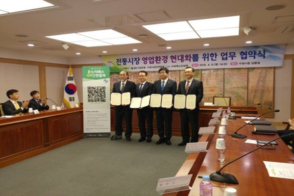Suwon-si will be the first local autonomous entity to introduce a mobile payment system with no fees.  (Starting from the left) Chairman Choi Geuk-ryol of Suwon-si's merchant union, Vice-Chairman Cho Young-hyun of Industrial Bank CIB Group, Mayor Yeom Tae-young of Suwon-si, and CEO Park Kyung-yang of HAREX INFOTECH took a commemorative picture after signing a MOU.