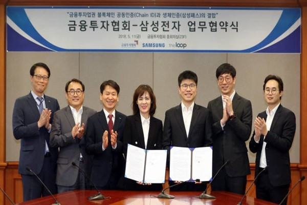 Representatives from Korea Financial Investment Association (KOFIA) and Samsung Electronics are showing their MOUs after exchanging them for combination of Samsung Pass and Chain ID.  Starting from the left: Department Head Kim Tae-ryong of KOFIA, Park Seon-moo who is an advisor to KOFIA's IT Committee, Director Kim Dae-jong of Korea Investment & Securities, Director Kim Jung-ah of KOFIA, Director Kim Jung-sik of Samsung Electronics, CEO Kim Jong-hyup of Theloop, and Director Kim Geun-jae of Daily Intelligence