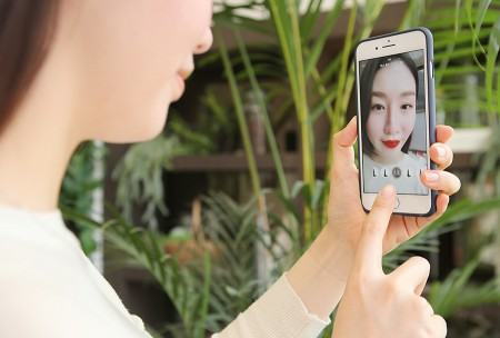 한 고객이 더현대닷컴 앱을 이용해 AR 메이크업 서비스를 이용해 가상으로 립스틱을 발라보고 있다. 사진=현대백화점 제공
