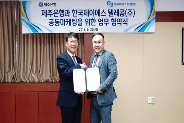 Vice-President Park Ho-ki (left) of Jeju Bank and CEO Lee Jong-seon of Korea JS Telecom are taking a commemorative picture after signing an agreement.