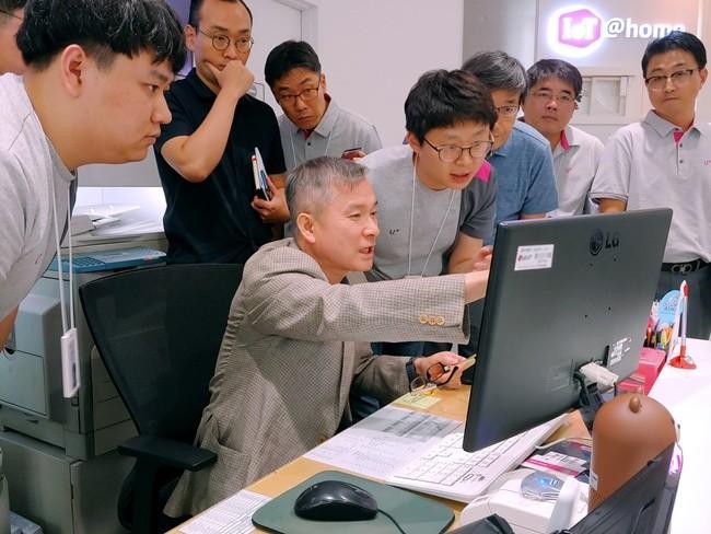 하현회 부회장이 강남직영점 직원에게 고객 맞춤 제안 시스템 설명을 듣고 있는 모습