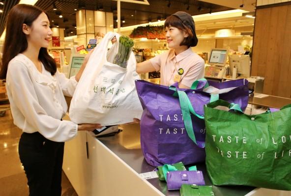 (현대백화점 무역센터점 식품관에서 캐셔 직원이 고객에게 구매한 식품을 친환경 소재의 장바구니(기본형)에 담아 전달하고 있다. 사진=현대백화점 제공