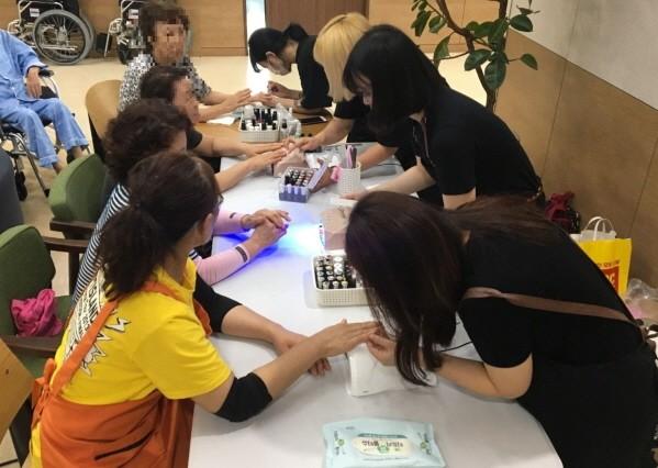 이투스교육 사내 '네일샵' 직원들이 일산복음병원에서 환자 및 보호자들에게 네일아트 봉사활동을 하고 있다. 사진=이투스교육 제공
