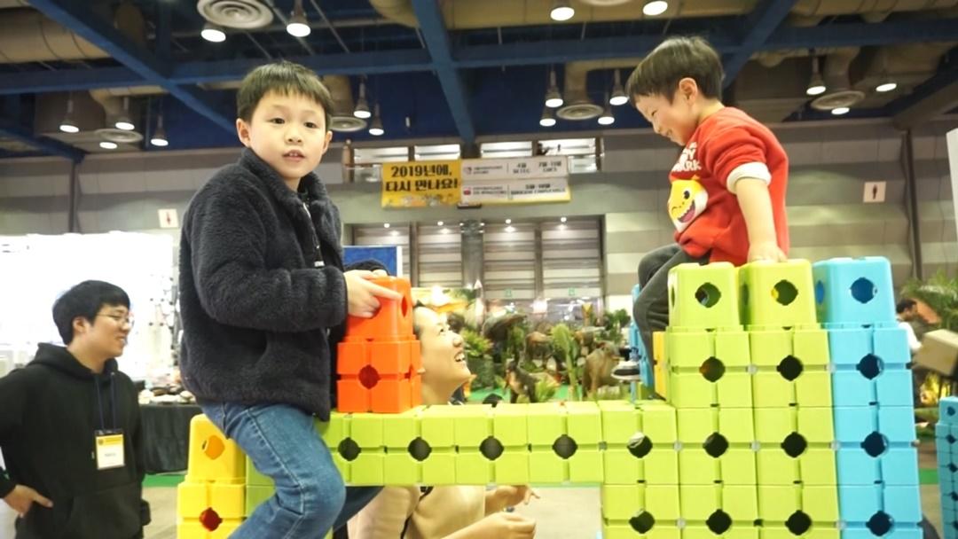아이가 직접 위토이즈 블록으로 지은 구조물 위에서 아무렇지 않게 놀고 있다.