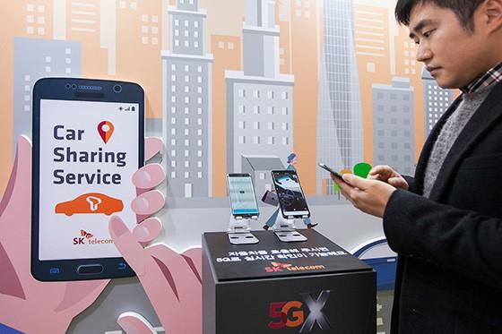 SK텔레콤 연구원이 K-시티 준공식 행사에서 5G 카셰어링 자율주행차를 호출하고, 자율주행차가 스스로 달리는 모습을 5G 스마트폰 영상통화로 보고 있다.