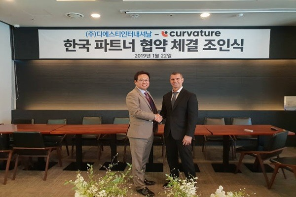 CEO Kim Hyung-tae (left) of DST International and Jason Ogden, who is the deputy general manager of APAC for Curvature, are shaking hands after signing an agreement.