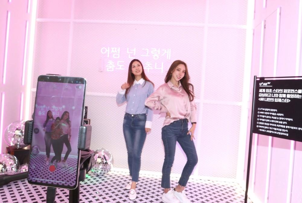 서울 강남역 인근에 마련된 U+5G 팝업스토어 '일상로5G길'에서 LG유플러스 모델들이 TV속 스타를 불러내 함께 춤을 추며 영상을 찍을 수 있는 'U+AR'을 즐기고 있다 [사진=LG유플러스]