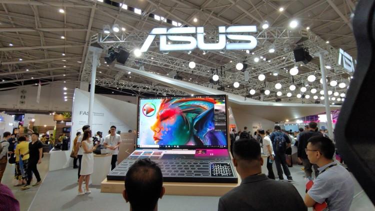 에이수스 직원들이 젠 북 듀오(ZenBook DUO)를 형상화한 대형 모형 앞에서 제품의 특장점을 설명하고 있다.