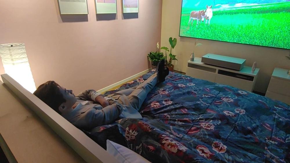 침실 룸에서 10cm 이내 간격 만으로 구현한 100인치 프로젝터 화면을 헨리가 침대에 누어 바라보고 있다.