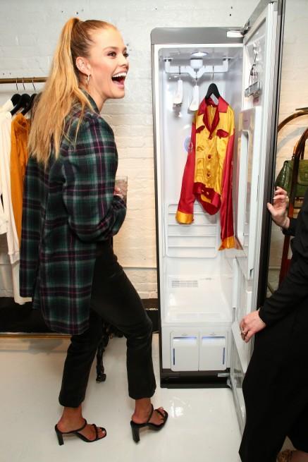 지난 3일부터 12일까지 미국 뉴욕 맨해튼에서 열린 '뉴욕패션위크'에서 슈포모델 니나 아그달이 전시된 LG스타일러를 살펴 보며 즐거워하고 있다.