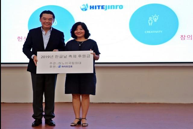 하이트진로 김인규 대표(왼쪽)가 지난 10월 3일, 베트남 하노이 국립외대를 방문해 한국어학과장 쩐티흐엉에게 한글날 축제 후원금을 전달하고 기념 촬영을 하고 있다.