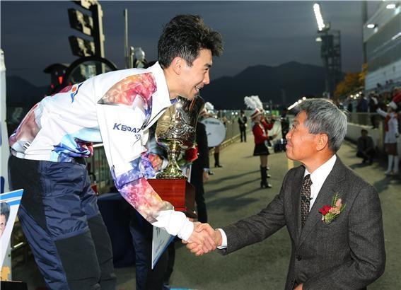 2018년 쿠리하라배 특별 경정에 참석한 쿠리하라 코이치로 선생이 우승을 차지한 조성인 선수에게 트로피를 수여하고 악수하고 있다.