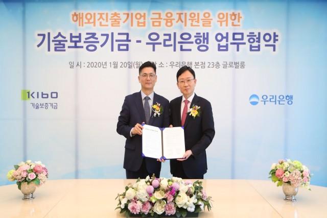 우리은행 서영호 글로벌그룹장(오른쪽)과 김영춘 기술보증기금 이사가 해외 진출기업 금융지원을 위한 양 기관의 업무협약을 맺은 후 기념 촬영을 하고 있다.