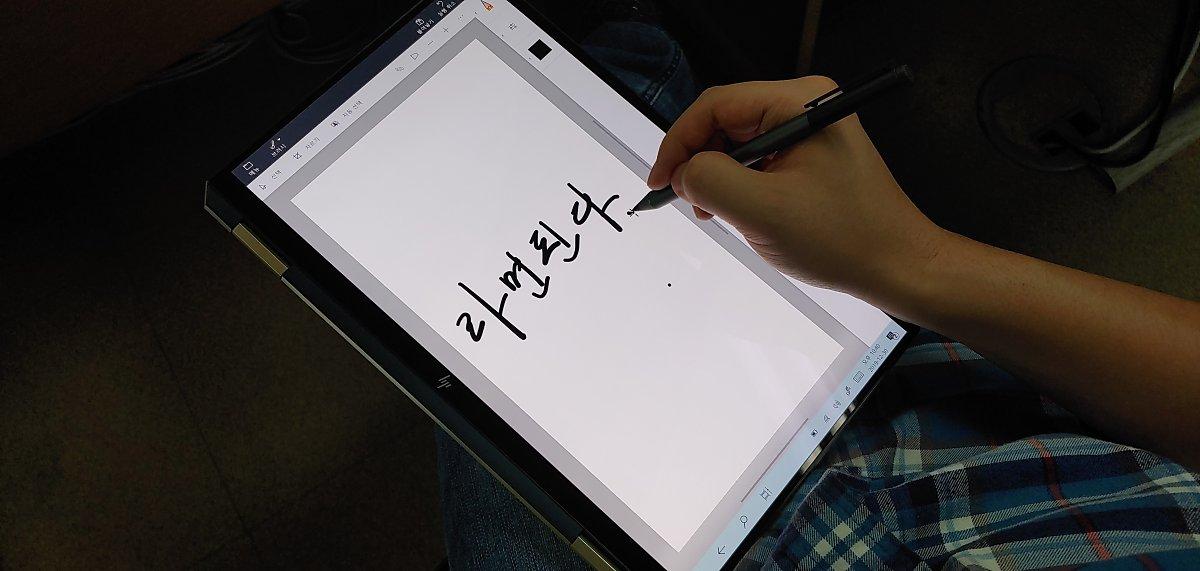 태블릿 모드에서 펜으로 붓글씨를 연습하고 있다.