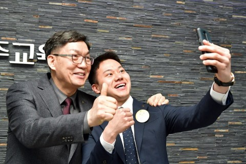 이대훈 농협은행장(왼쪽)과 신입행원이 특강이후 핸드폰으로 기념사진을 찍고 있다.