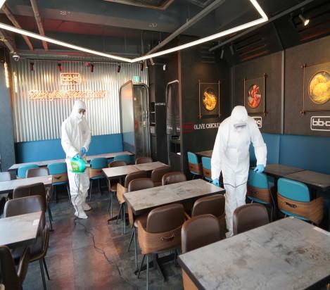 10일 오전 제너시스BBQ헬리오시티점에서 방호복과 마스크를 쓴 방역업체 직원들이 매장을 소독하고 있다. 출처=제너시스BBQ