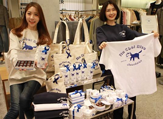 11일 오전 롯데백화점 본점에서 모델들이 '오샤블루 맨투맨, 에코백, 초콜릿'를 소개하는 모습출처=롯데쇼핑