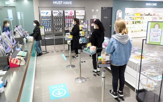 올리브영 명동 플래그십 스토어에 부착된 '발자국 스티커'에 맞춰 고객들이 줄을 서고 있는 모습 출처=올리브영
