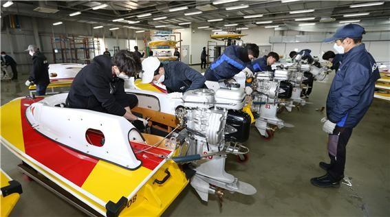 경정 선수들과 직원들이 경주정에 모터를 장착하며 성능을 점검하고 있다.