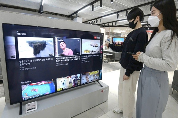 It is shown that 8K TVs from Samsung Electronics and LG Electronics are the only ones that support AV1 hardware decoding, which is a codec for YouTube's 8K service, enabling owners to watch 8K streaming videos on YouTube.  Consumers at Lotte Hi-Mart's megastore is looking at an 8K TV from LG Electronics.  Staff Reporter Lee, Donggeun | foto@etnews.com