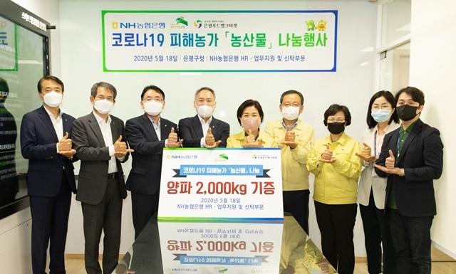 농협은행 HR 업무지원 부문 임직원이 은평구청에 농산물을 기증하는 나눔 행사를 벌이고 기념 촬영을 하고 있다.