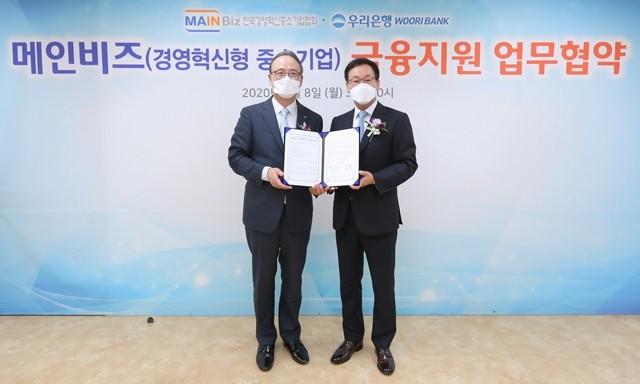 우리은행이 메인비즈협회와 금융지원 업무협약을 맺고 있다.박완식 우리은행 중소기업그룹장(오른쪽)과 석용찬 메인비즈협회장이 기념촬영을 하고 있다.