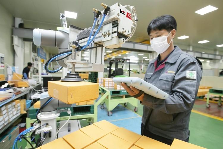 충북 제천에 있는 박원 공장에서 생산직 근로자가 KT 5G 스마트팩토리 코봇과 함께 작업하고 있다. [사진=KT]