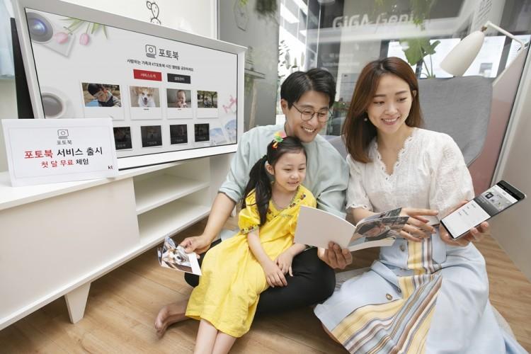모델들이 사진앨범과 올레tv 디지털 포토북으로 감상할 수 있는 '포토북' 서비스를 소개하고 있다. [사진=KT]